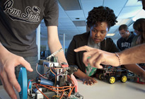 A female students works with other students in an engineering classroom