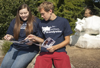Two students, female and male, site outdoors looking at printed brochures