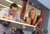 Two students (male and female) cut a sheet of material with an electric saw in an engineering classroom